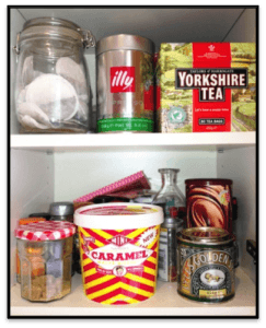Tea, coffee and biscuits in a cupboard.